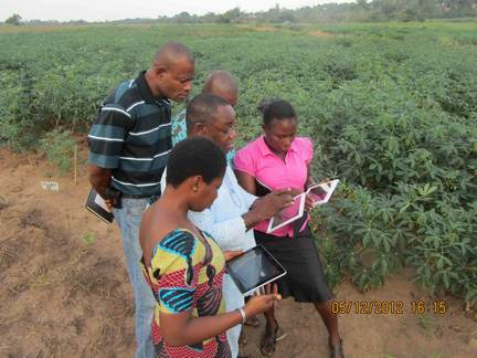Fastfoward to 2012: Based on feedback, a larger electronic tablet was favoured over the smaller handheld device. Yemi (centre) takes field staff through the paces in tablet use.
