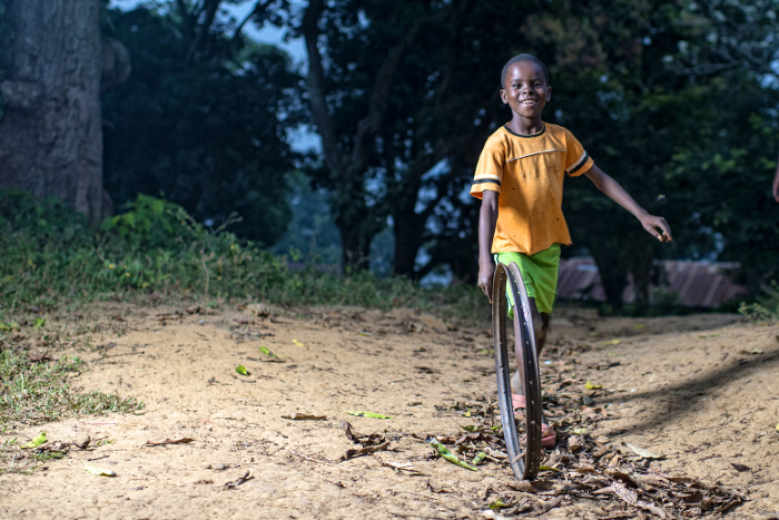 A boy plays with an improvised hoop in Lukolela, Democratic Republic of Congo.