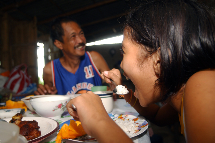A girl eats rice with her family in the Philippines.