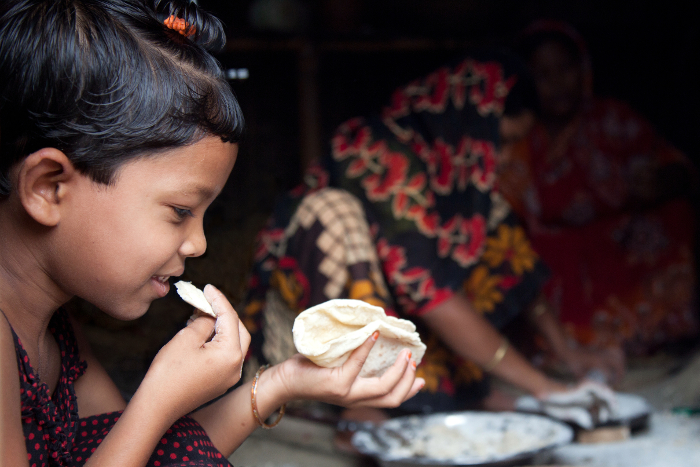 A little girl eats fresh roti at home in the district of Dinajpur, Bangladesh.